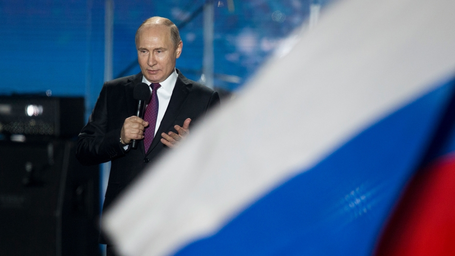 Russian President Vladimir Putin is shown speaking into a microphone and wearing a dark suit.