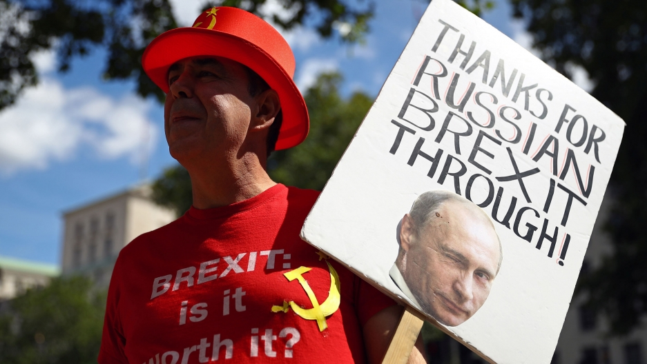 "A man wearing a red top hat with the Russian hammer a sickle is shown holding a sign that says, ""Thanks for the Russian Brexit through."
