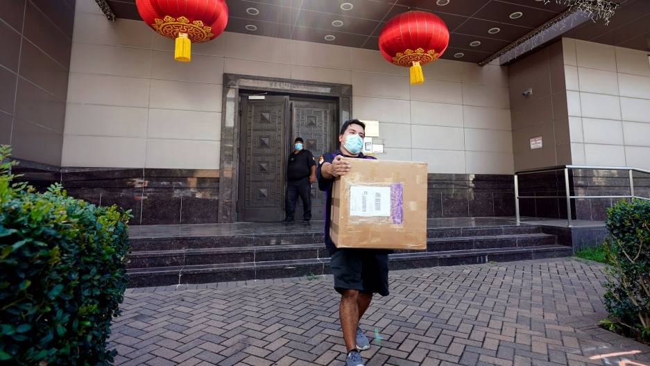 A man is shown wearing a face mask and carrying a large brown cardboard box with the doors of the Chinese Consulate in Houston in the background.