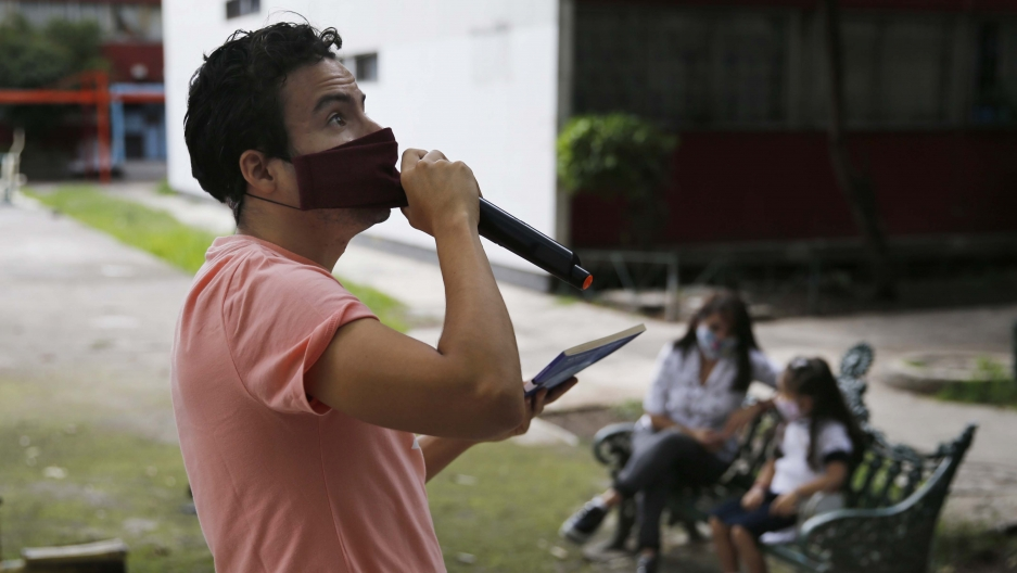 Residents listen from a bench, background, as Percibald García reads children's books aloud outside the high-rise buildings in the Tlatelolco housing complex, in Mexico City, on July 18, 2020.