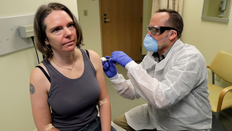 A woman is shown wearing a tank top and sitting while receiving an injection from a medical professional.