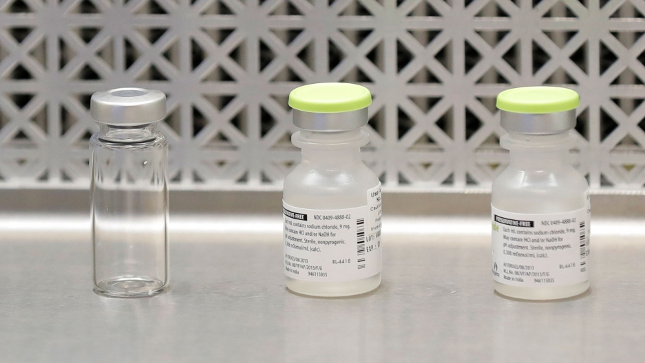 Three vials are show sitting on a table with two of the bottles have a label.