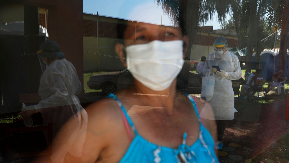 A woman is shown with a face mask and wearing a blue top and looking through glass where several people are shown wearing full medical protective gowns.