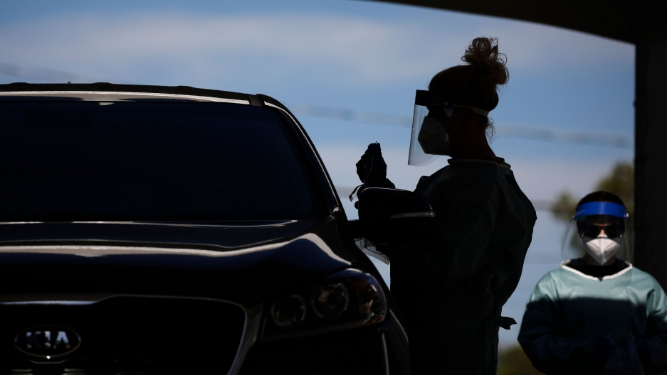 A healthcare worker is shown in shadow standing next to a car and wearing a protective face shield.