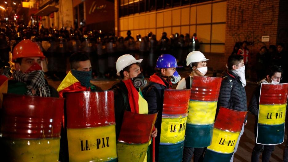 Demonstrators with makeshift shields protest against President Evo Morales' reelection, in La Paz, Boliva, Nov. 6, 2019.