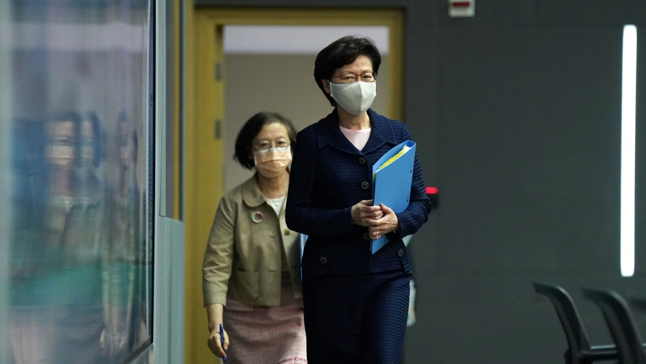 Hong Kong Chief Executive Carrie Lam is shown walking into a room and holding a blue folder.