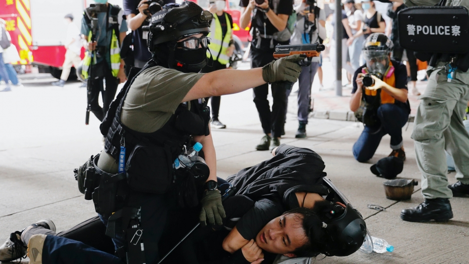 Riot police use water cannon to disperse protesters and one officer presses down on a protester