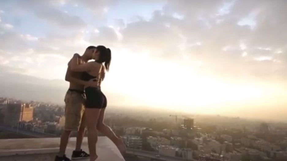 A man kisses a woman wearing blach shorts on a rooftop overlooking a pink skyline