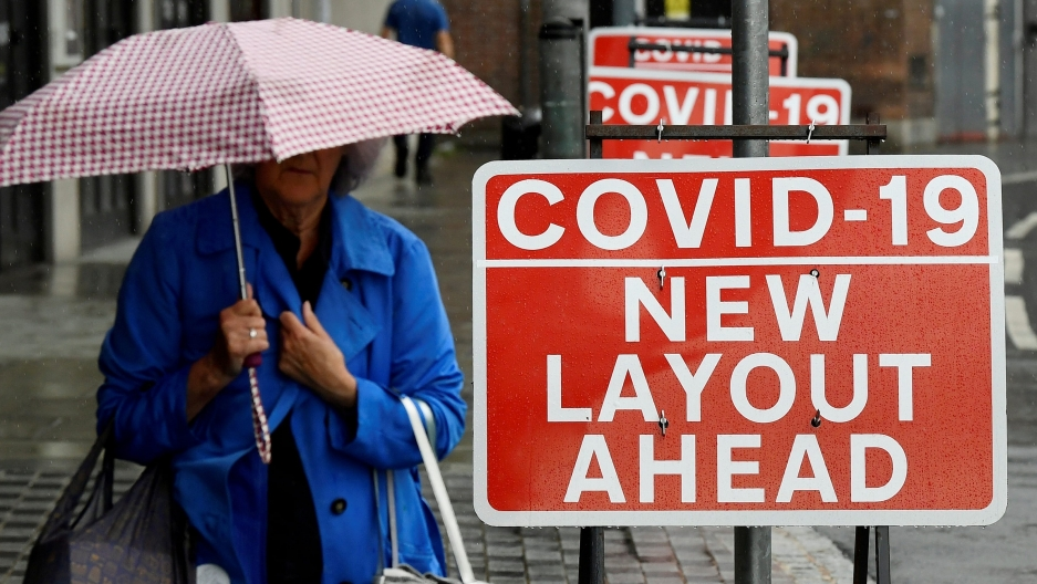 A woman holds shopping bags and an umbrella next to bright red sign with white text about COVID-19