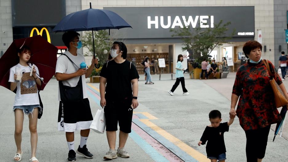 People wear face masks in in Beijing while walking outside near a Huawei store.