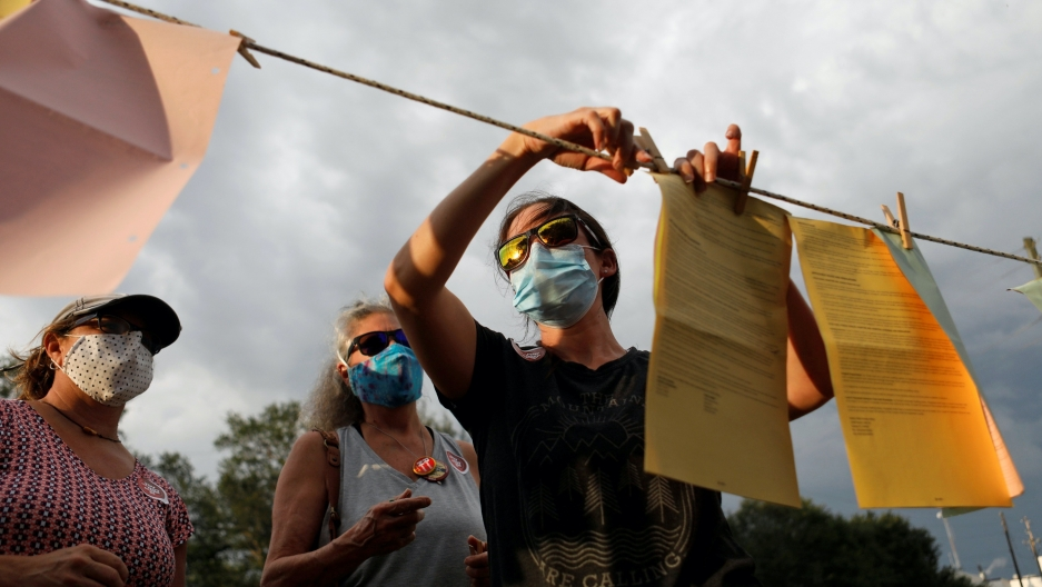 Three women wearing masks hang signs on a laundry wire.