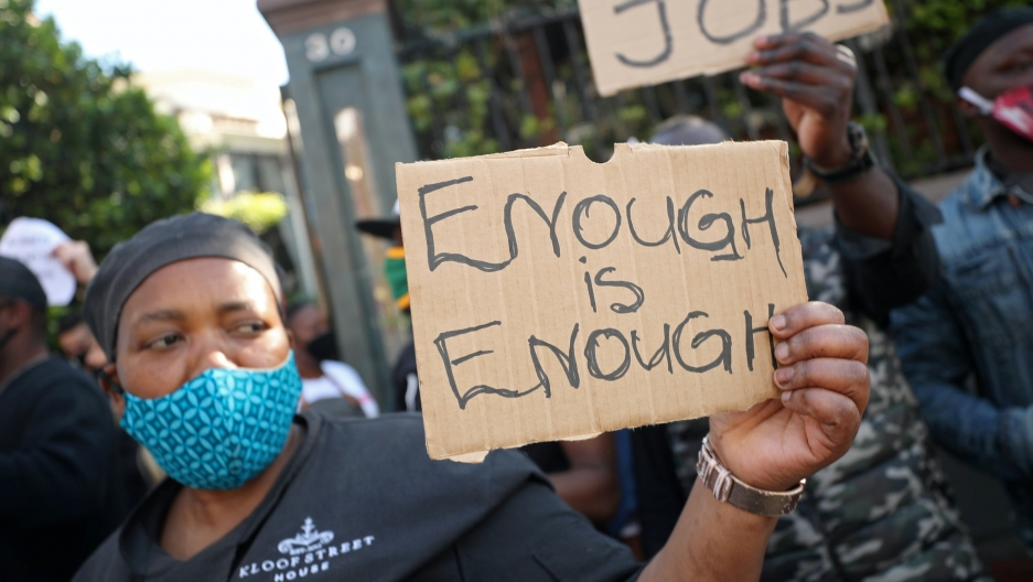 "A Black African woman wears a blue face mask and holds a brown sign that reads ""enough is enough."""