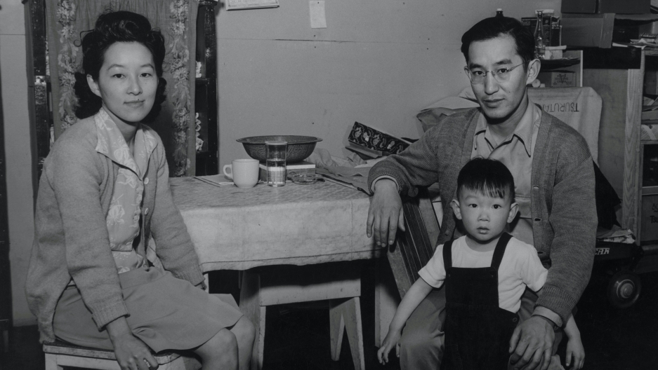 A black and white photo of a Japanese family (woman, man, child) sitting in a kitchen setting.