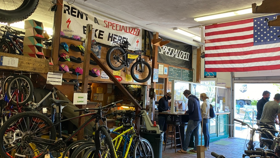 Inside of a bike shop with a large American flag in sunlight