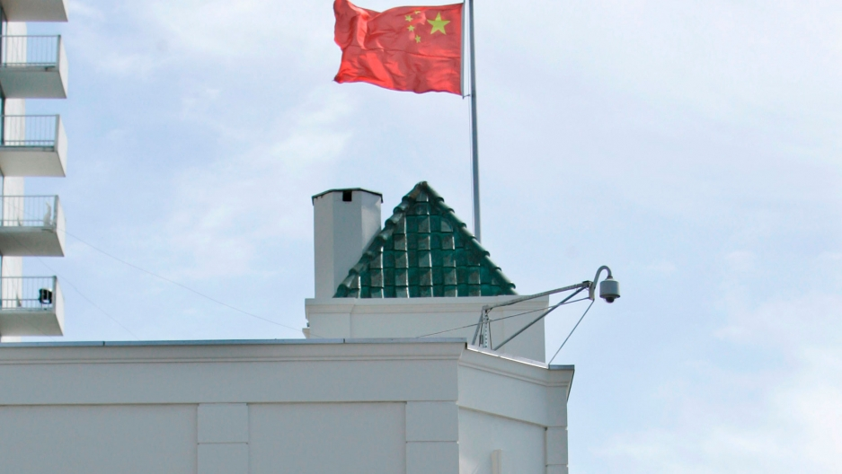 The top of a white building is shown with a Chinese flag flying.