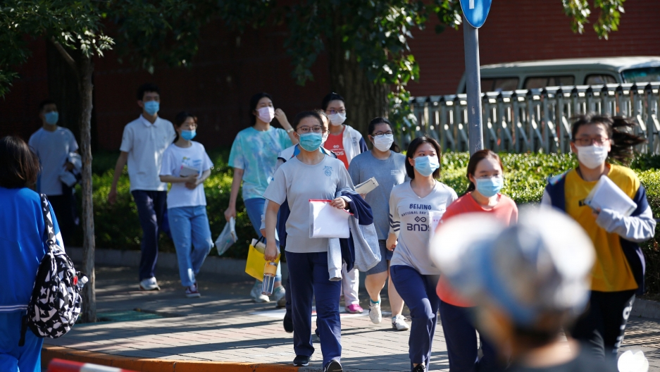"Students wearing face masks walk in line to enter a high school as they take part in the annual national college entrance exam, or ""gaokao"", which has been postponed by one month due to the coronavirus disease (COVID-19) outbreak, in Beijing, China July 7"
