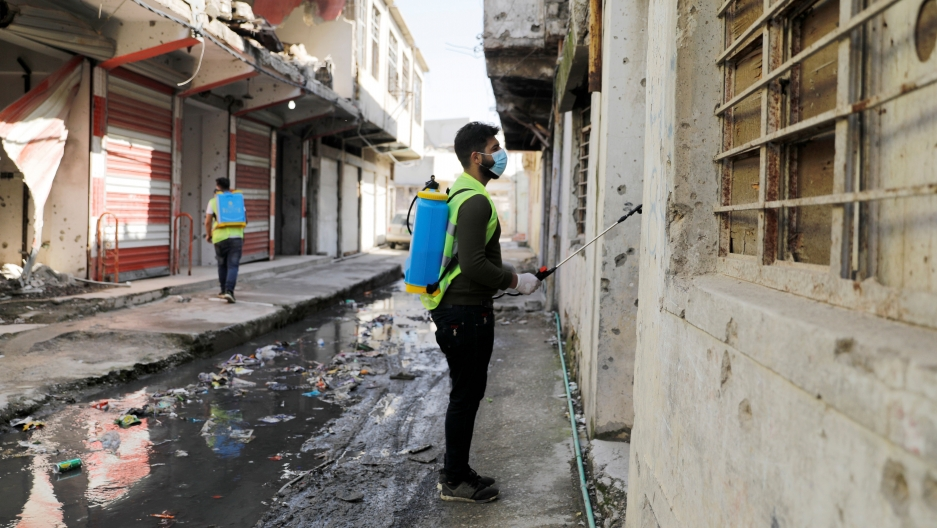 Iraqi young volunteers spray with disinfectants to combat an outbreak of coronavirus during a curfew imposed by Iraqi authorities, in the old city ofMosul, Iraq, March 15, 2020.