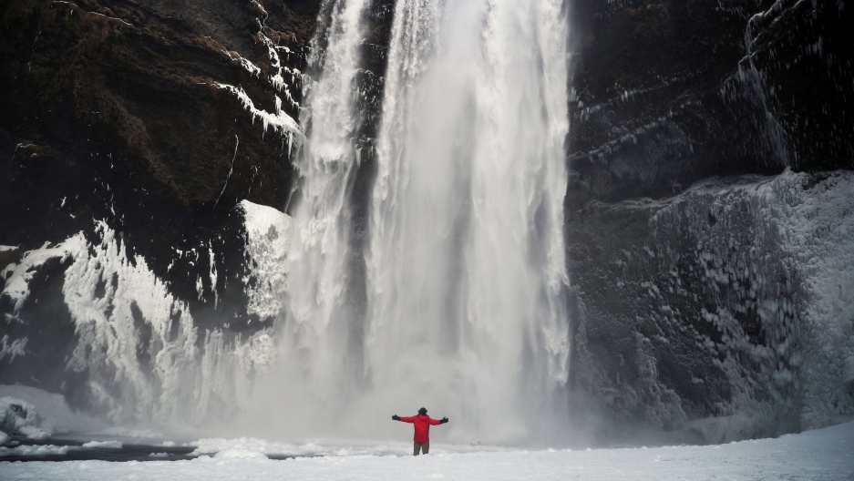 A man stands in front of the Skogafoss waterfall in Skogar, Iceland, March 8, 2020.