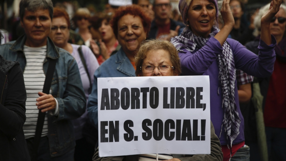 "A woman holds a banner that reads ""Free abortion covered by social security"" during a pro-choice march to celebrate the government ending its plan to reform Spain's abortion law in Madrid September 28, 2014. Spanish Prime Minister Mariano Rajoy on Tuesday"