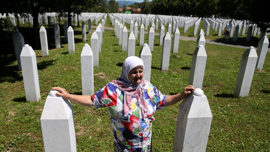 A woman stands at a memorial.