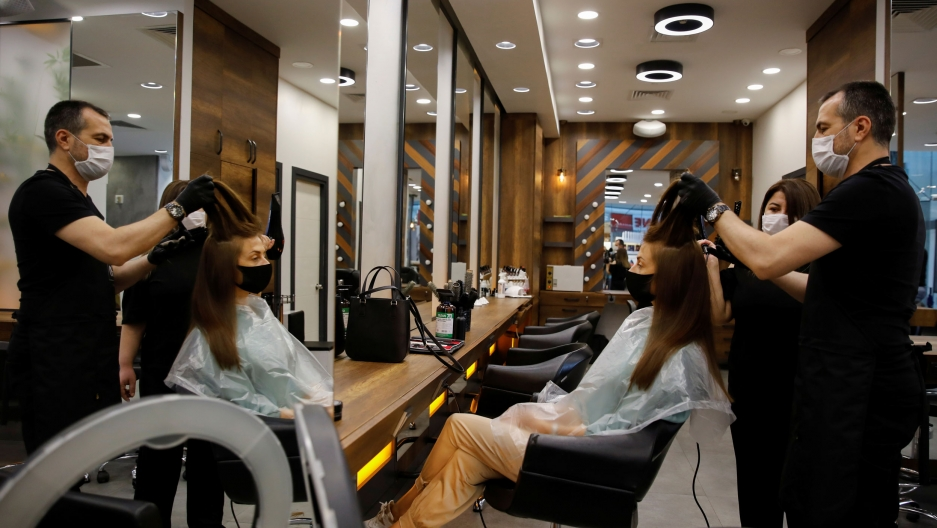 A hairdresser is shown standing behind a customer who is sitting in a chair while he holds her hair up in the air.