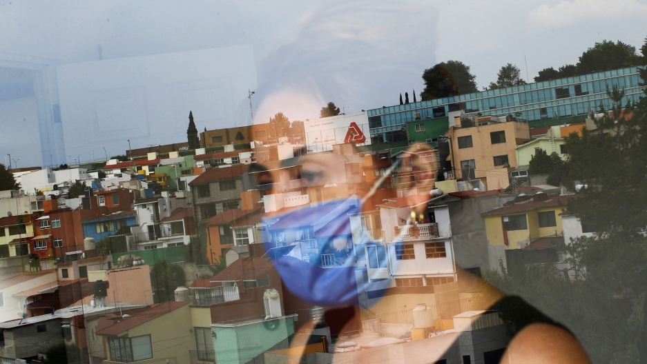 A woman is shown through a clear glass window with the reflection of a Mexico City neighborhood.