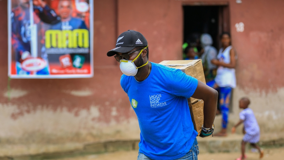 """A man is shown wearing a blue shirt with """"Lagos Food Bank"""" written on it while carrying a cardboard box on his back."""