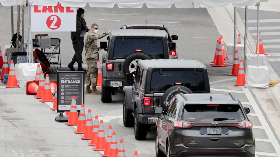 A line of vehicles are shown next to a row of orange traffic cones leading to a National Guard official at a mobile coronavirus testing facility.