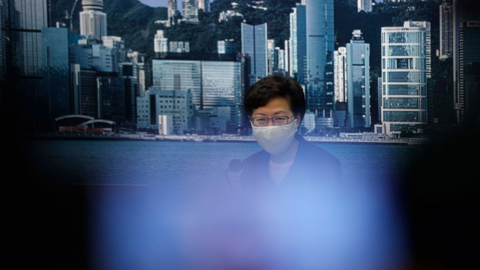 Hong Kong Chief Executive Carrie Lam is shown wearing a face mask with an image of the Hong Kong coastline in the background.