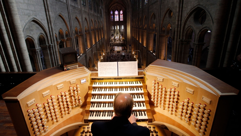 A man is shown from behind sitting at Notre Dame's organ with five rows of keys.