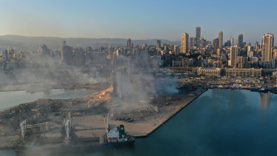 A view of Beirut's port is shown, flattened from an explosion and smoke rising from the rubble