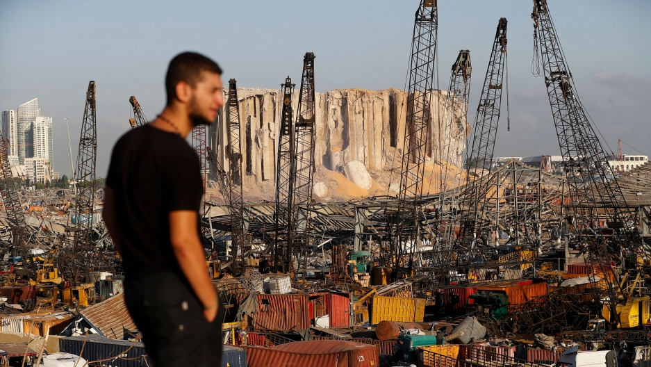 The port of Beirut is show with shipping containers scattered and damaged in the distance with a man in a dark t-shirt in the nearground.
