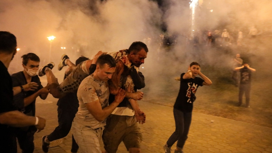 Several people are shown carrying an injured protester on their shoulders with smoke all around them.