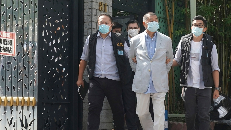 Hong Kong media tycoon Jimmy Lai is shown with his arms tied behind his back and being escorted by four other men all wearing face masks.