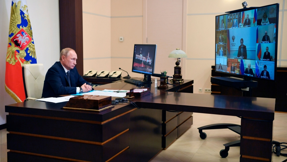 Russian President Vladimir Putin attends a virtual cabinet meeting while sitting at a large wooden desk with a television monitor showing several officials.