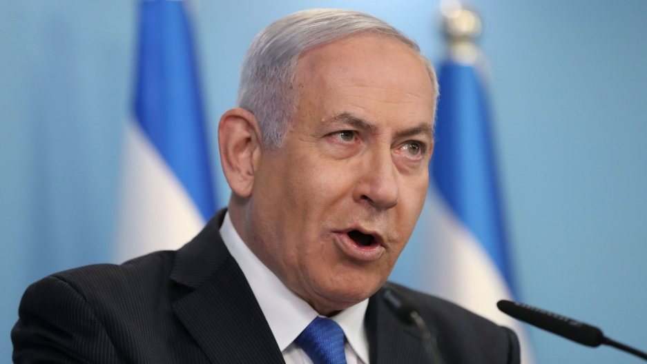 Israeli Prime Minister Benjamin Netanyahu is shown wearing a dark suit and blue tied while speaking into a microphone.