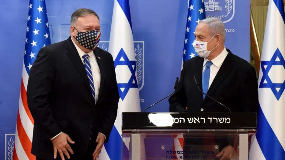 US Secretary of State Mike Pompeo is shown standing next to Israeli Prime Minister Benjamin Netanyahu who is standing behind a podium, both wearing masks.