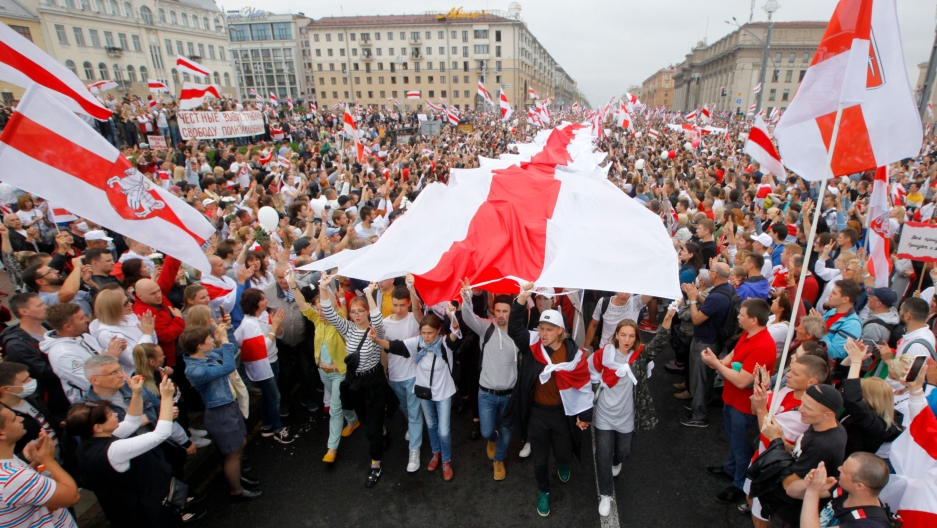 A large crowd of people are shown filling Independence Square in Minsk with a long traditional red and white flag streaming through the middle.