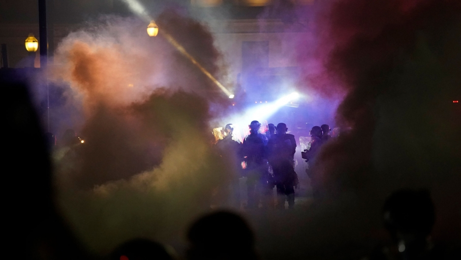 Police in riot gear clear the area in front of Kenosha County Courthouse during clashes with protesters in Kenosha, Wisconsin, Aug. 25, 2020.