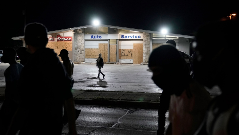 Several people are shown in shadow with a automobile service center stands in the background with boarded up windows.
