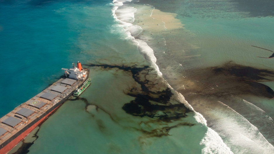 A long, narrow boat leaks black oil into the Indian Ocean off coast of Mauritius blue waters