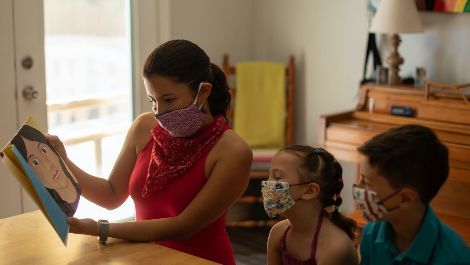 A woman wears a mask and reads a book to two children, also wearing masks.