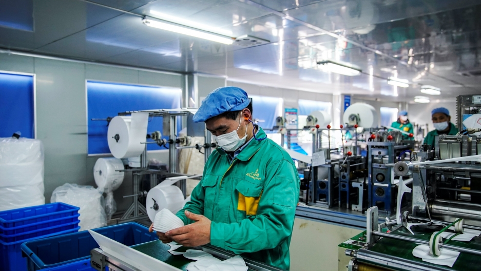 A person wears a mask on an assembly line at a factory