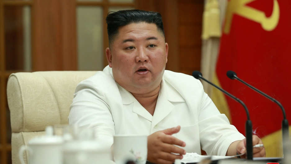 NorthKorean leader Kim Jong-un, with a white suit and black flat-top hair style, speaks at a conference table.