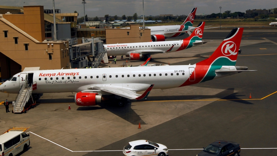 Several white airplanes with Kenya Airways logo on them in red and green parked in airport.