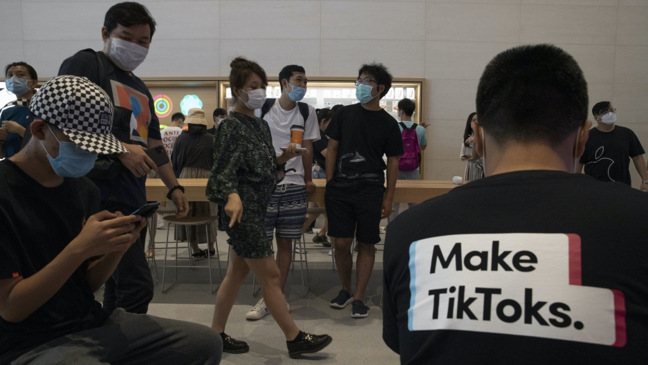 "Several people are shown in an Apple store in Beijing with one person in the near ground wearing a t-shirt with ""Make TikToks"" printed on it."