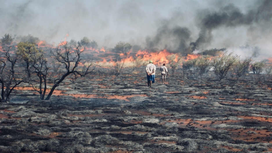Two people standing in a dry area in front of a wildfire