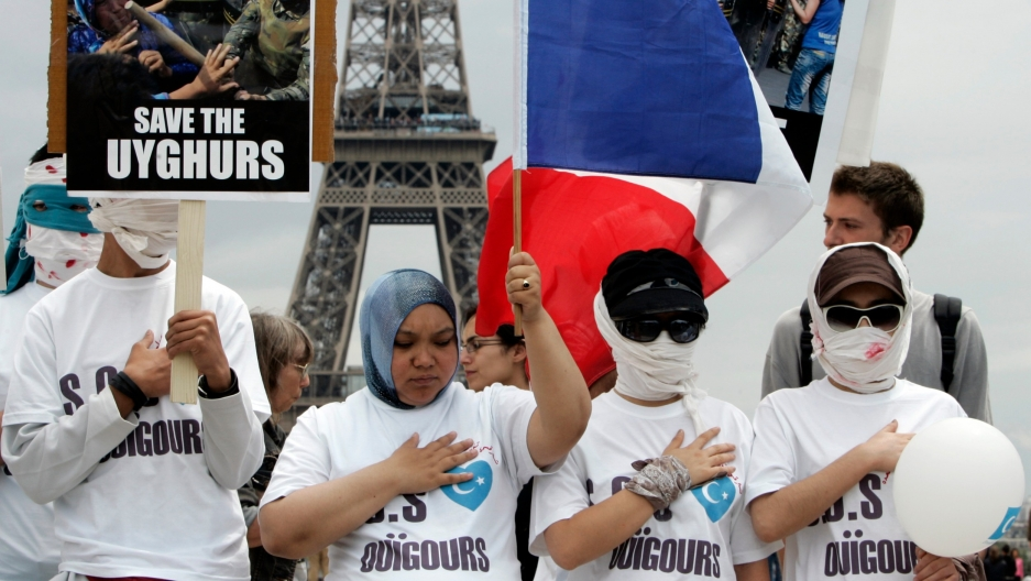 Uighur protesters, wearing bandages over mock wounds, hold placards and wave a French flag as they take part in a demonstration condemning violence in China's Xinjiang province, at the Trocadero near the Eiffel Tower in Paris, France, July 8, 2009.
