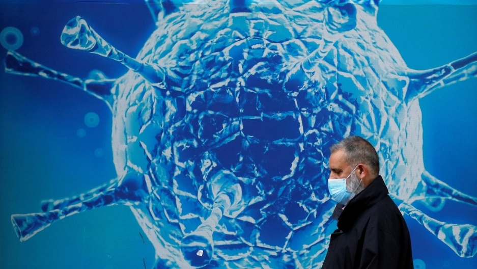 A man wearing a protective face mask walks past an illustration of a virus outside a regional science centre amid the coronavirus disease (COVID-19) outbreak, in Oldham, Britain, August 3, 2020.