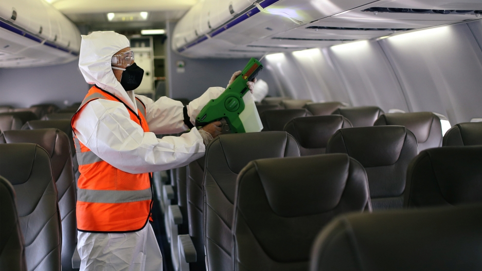 A person wearing a hazmat suit appears cleaning inside an airplane.